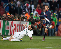 The USA's Landon Donovan shoots the first goal as Slovenia defender Marko Suler slides in during the second half of the 2010 World Cup match between USA and Slovenia at Ellis Park Stadium in Johannesburg, South Africa on Friday, June 18, 2010.  The USA tied Slovenia 2-2.