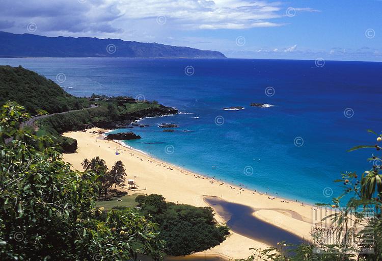 Overview of white sand beach and clear blue water of Waimea Bay, Oahu, Hawaii