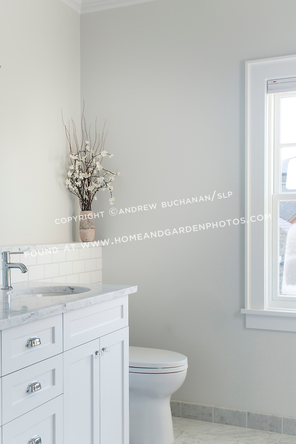 White vanity and pale grey marble create a crisp clean look in this new bathroom.