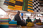 A Fulani man sells strips of cloth woven together into colorfully-patterned breakfasts in the market in Segou, Mali.