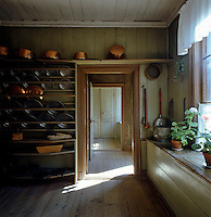 Copper pots and pewter plates are stored on racks on the wall of the kitchen