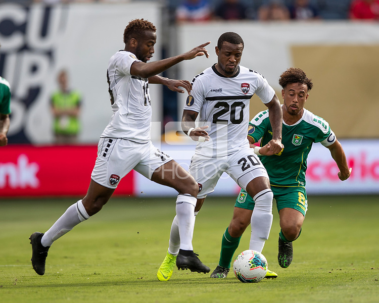 KANSAS CITY, KS - JUNE 26: Jomal Williams #20, Kevin Molino #10 and Samuel Cox #8 all go for the ball during a game between Guyana and Trinidad