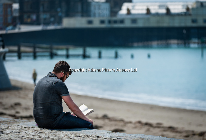 HOT WEATHER WALES Aberystwyth, Ceredigion, West Wales. UK Weather Wednesday  8th June 2016: With yellow warnings for rain across swathes of England the sun comes out at lunchtime with temperatures reaching 19 degrees Celsius after a dull morning. A student enjoys the sun whilsy catching up on some reading.