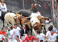 Participants run with a El Pilar fighting bulls during the sixth San Fermin Festival´s running of the bulls, on July 12, 2013, in Pamplona, Basque Country. On each day of the eight San Fermin festival days six bulls are released at 8:00 a.m. (0600 GMT) to run from their corral through the narrow, cobbled streets of the old navarre town over an 850-meter (yard) course. Ahead of them are the runners, who try to stay close to the bulls without falling over or being gored. (Ander Gillenea / Bostok Photo)