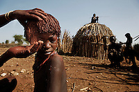 A child in the Hamar village called Logira gets her hair done before a wedding.  Hamar have a distinctive hairstyle that involves curling the hair with a mixture of butter and ochre clay.