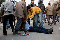An anti-government protester lies on the ground injured in violent clashes with pro-Mubarak supporters in Tahrir Square. Continued anti-government protests take place in Cairo calling for President Mubarak to stand down. After dissolving the government, Mubarak still refuses to step down from power.