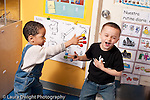 Educaton preschool 3-4 year olds two boys playing with beads stuck on fingertips pretend play superhero powers gender typical