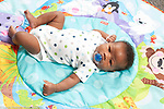 newborn baby boy 7 weeks old on back reflex tonic neck (fencing), pacifier in mouth