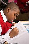 K-8 Parochial School Bronx New York Grade 4 boy writing in notebook in class vertical