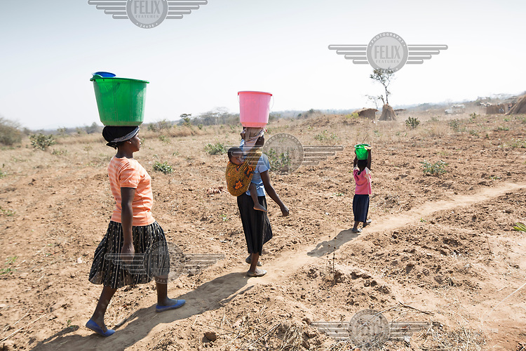 Isabel Mvula (34) Mphatso Mwali (24) and Cathrine (3) carry water home after collecting it from a dry river bed.