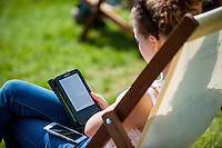 Hay on Wye, UK. Sunday 29 May 2016<br /> Pictured:  A young woman reads using an electronic device at the festival<br /> Re: The 2016 Hay festival take place at Hay on Wye, Powys, Wales