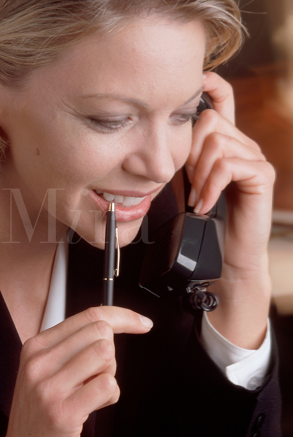 A smiling business woman talking on the phone; close up.