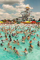 Swimmers cool off in the 20-acre Boomerang Bay water park at Carowinds theme Park near Charlotte, NC. Seen here is Bondi Beach, a 600,000-gallon, 34,000 square-foot wave pool that provides a fresh-water surf-like experience. The water attractions are part of Carowinds, a 112-acre theme park (amusement park) located on the state lines between North Carolina and South Carolina. The theme park is a popular summer Carolina attraction, one of three major theme parks in the Carolinas. Seen in the back right corner of the photo is Pipeline Peak, a complex of four enclosed water slides, including two body slides and two inner-tube slides.