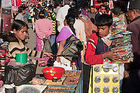 Kathmandu, Nepal.  Street Vendors.  Young Man Considers Popcorn, Peanuts, and other Snacks Sold by Young Woman
