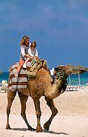 Tunesien, Djerba, Plage de Sidi Mahrés, Mutter und Kind reiten auf Kamel