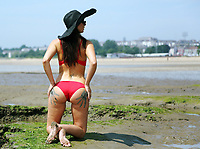 FAO ADRIAN, SUN PICTURE DESK<br /> Natasha Bunce with mud hand prints on her bum at Swansea Bay, Wales, UK