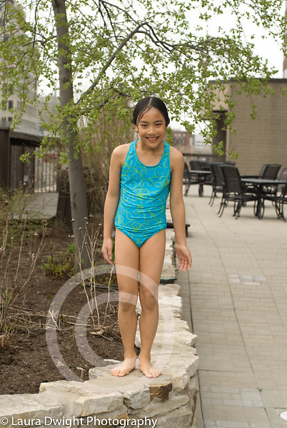 7 year old girl outside posing on wall in bathing suit