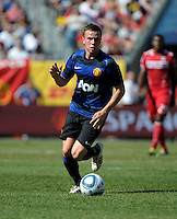 Manchester United midfielder Tom Cleverly (35) dribbles the ball.  Manchester United defeated the Chicago Fire 3-1 at Soldier Field in Chicago, IL on July 23, 2011.