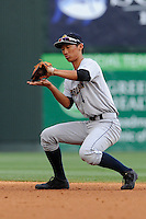 Second baseman Gosuke Katoh (4) of the Charleston RiverDogs grabs a grounder in a game against the Greenville Drive on Wednesday, June 11, 2014, at Fluor Field at the West End in Greenville, South Carolina. Katoh is the No. 10 prospect of the New York Yankees, according to Baseball America. Greenville won, 6-3. (Tom Priddy/Four Seam Images)