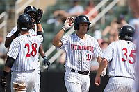Seby Zavala (21) of the Kannapolis Intimidators is congratulated as he returns to the dugout after hitting a home run against the West Virginia Power at Kannapolis Intimidators Stadium on June 18, 2017 in Kannapolis, North Carolina.  The Intimidators defeated the Power 5-3 to win the South Atlantic League Northern Division first half title.  It is the first trip to the playoffs for the Intimidators since 2009.  (Brian Westerholt/Four Seam Images)