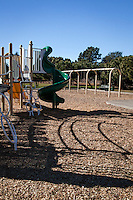 A green slide and other play equipment cast their shadows on and empty playground under a clear, blue sky.