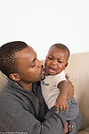 5 month old baby boy crying upset comforted by father vertical African American