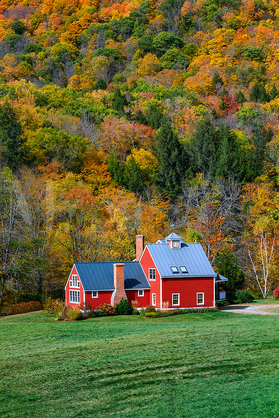 Charming red house flanked by autumn foliage, Bridgewater, Vermont, USA.