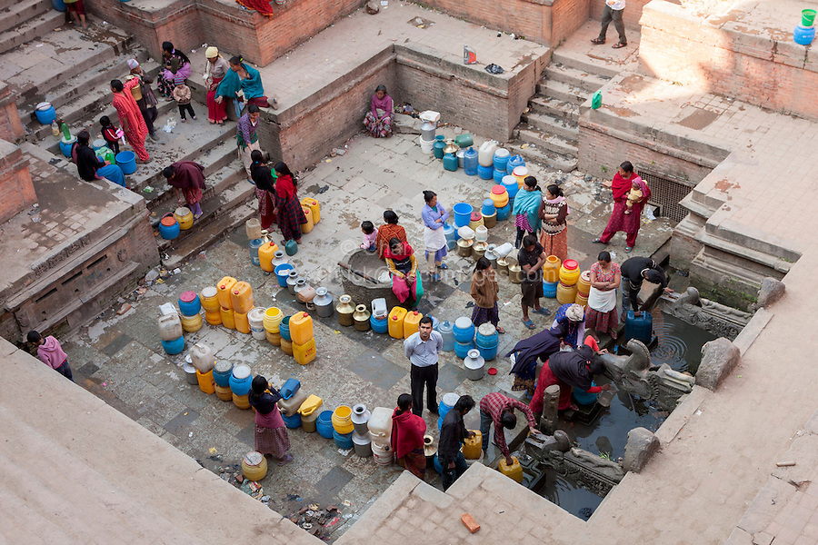 Nepal, Patan.  Men and Women Lined up at the Manga Hiti, one of the Public Water Fountains Serving Residents who have no Running Water in their Houses.