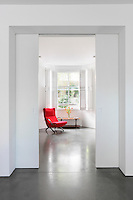 A view through a pair of partly open sliding doors to a minimalist living room beyond. A red chair provides a vibrant spot of colour in contrast to the white room.