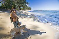 Young Asian American woman walking dogs on white sand beach with blue water, North Shore of Oahu