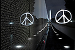 """Using a photographic technique called """"painting with light,"""" the peace symbol is burned into the night at the Vietnam Memorial in Washington, DC, Washington monument in the background."""