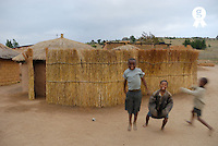 Three children (6-8) jumping by huts, smiling, portrait (Licence this image exclusively with Getty: http://www.gettyimages.com/detail/200503592-001 )