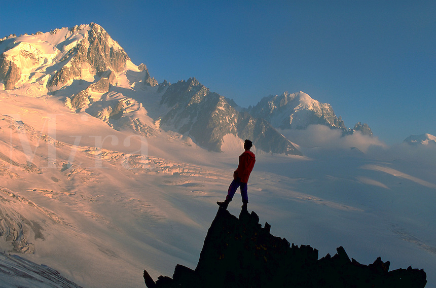 A climber standing on a rock outcropping admiring the sunrise below Aigulle Du Chardonnet, French Alps.