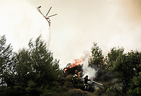 Pictured: Firemen battle with the flames while a fire service helicopter douses the flames with water.<br /> Re: A forest fire has been raging in the area of Kalamos, 20 miles east of Athens in Greece. There have been power cuts, country houses burned and children camps evacuated from the area.