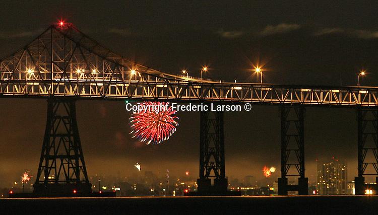 Seasonal July fireworks explodes under the Richmond San Rafael Bridge in California.