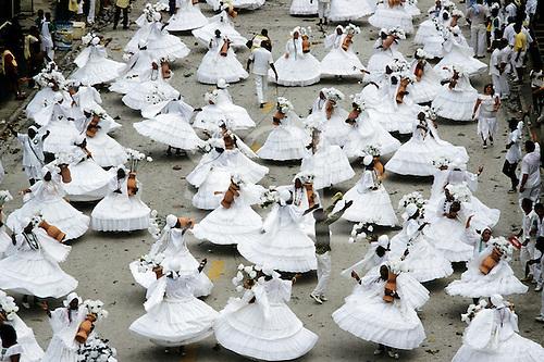 Rio de Janeiro, Brazil. Carnival parade; ala das Bahianas section, in white dresses holding vases of flowers.