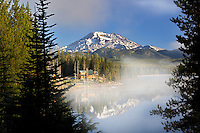 South Sister Mountain reflected in Elk Lake with cabin. Central Oregon