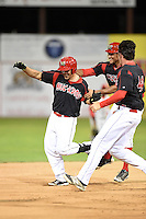 Batavia Muckdogs outfielder Victor Castro (40) is mobbed by teammates including Josh Hodges (44) and Kevin Grove (12) after a walk off hit during a game against the Brooklyn Cyclones on August 11, 2014 at Dwyer Stadium in Batavia, New York.  Batavia defeated Brooklyn 4-3.  (Mike Janes/Four Seam Images)