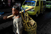 Market worker with his basket walking through the main bazaar in Ambon City, where Christians and Muslims live and trade side by side. The 1999-2002 religious war between Maluku's Christian and Muslim populations, mainly centred on Ambon Island, led to over 5000 deaths and to around 500,000 people become displaced. Destroyed homes and offices, churches and mosques are slowly being either torn-down or renovated.  Urban centres, such as Ambon City, continue to be split along largely sectarian lines, and tensions are never far below the surface. Riots between Christian and Muslim youths erupted in September 2011 and, most recently, June 2012, though luckily simmered down just as quickly, partly due to community leaders learning how to defuse tensions from the earlier, more devastating, conflagration. /Felix Features