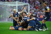 London, England - Thursday, August 9, 2012: The USA defeated Japan 2-1 to win the London 2012 Olympic gold medal at Wembley Arena. Carli Lloyd is congratulated after scoring her first goal. .