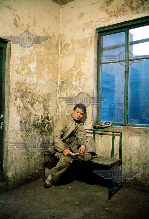An industrial worker at a coal coking plant on a short break during his shift. The workers at this factory earn approximately 1000 RMB (the equivalent of approximately 100 US$) per month on average. They usually work eight-hour shifts every day of the week.