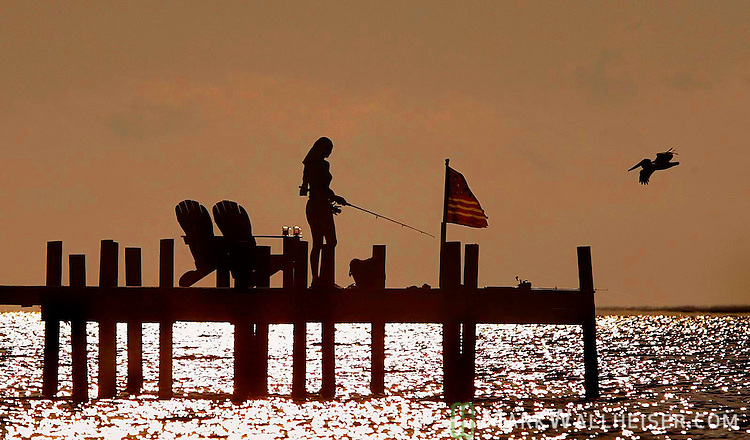 A woman fishes from a dock in the Apalachicola Bay along the Florida Panhandle.    (Mark Wallheiser/TallahasseeStock.com)