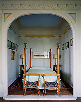 The early 19th-century four poster bed, features decorative urns atop the posts and is cocooned in an alcove painted with trompe l'oeil wall hangings