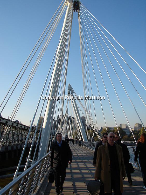 London, England - November 6, 2006:  Pedestrians cross Hungerford Bridge over the Thames.