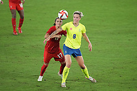 YOKOHAMA, JAPAN - AUGUST 6: Jessie Fleming #17 of Canada battles for the ball with Lina Hurtig #8 of Sweden during a game between Canada and Sweden at International Stadium Yokohama on August 6, 2021 in Yokohama, Japan.