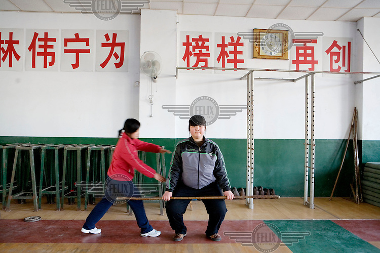 A new student being coached at weight-lifting at the Weifang City Sports School, one of 3,000 state-run athletic academies that consign nearly 400,000 youngsters to a form of athletic servitude. In the category of weight-lifting, many of these students come from farming communities. They have been hand picked by sports scouts who travel to far away provinces visiting schools whilst taking detailed measurements of potential atheletes. There is more of a focus on finding girls as research by the Chinese state suggests that it is easier to win Olympic gold medals in this area. They measure shoulder width, thigh length and waist circumference - and if everything fits, these young students are told they have the honour of serving their motherland.