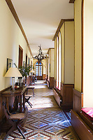The gothic windows and a chandelier made entirely from antlers are quirky touches to this elegant hallway
