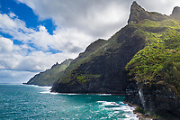 High cliffs and a waterfall on Kaua'i's Na Pali coastline.
