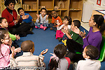 Education preschool 4 year olds circle time music activity singing and clapping hands two female teachers horizontal