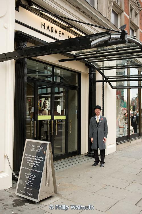 A doorman in uniform outside a Harvey Nichols store in Kinghtsbridge, London.
